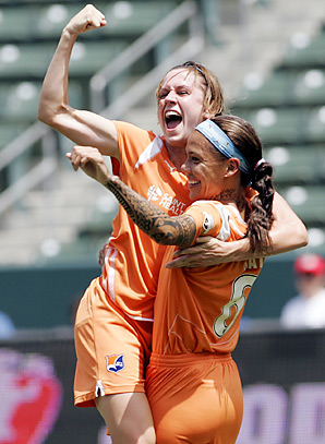 Heather O'Reilly being congratulated by teammate Natasha Kai after scoring the game-winner